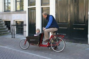 Successful expats ride bicycles in Amsterdam