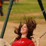 Young woman enjoying herself on a playground swing