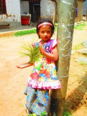 Girl playing with a plant in Bumthang