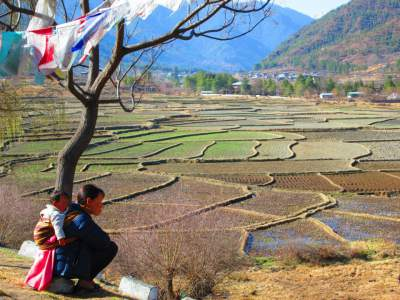 Woman with baby overlooking fields in Paro